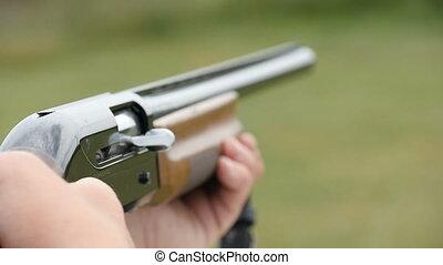 Skeet shooting shotgun aiming and shooting somewhere in...