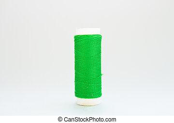 skein of green thread on a white background