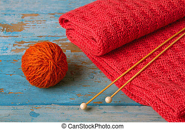 Skein of wool red knitted scarf and knitting needles