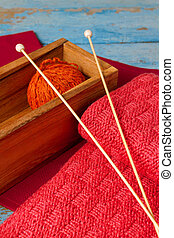 Skein of wool, spokes and a red knitted scarf