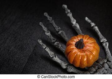 Skeleton hand holding pumpkin