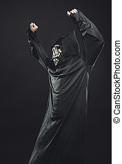 skeleton in a black robe with glasses dancing