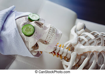 Skeleton in Spa salon with towel on her head and mask on her...