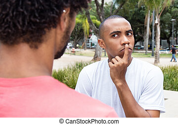 Skeptical african american man in discussion with friend