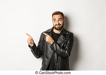 Skeptical and doubtful guy in black leather jacket, shrugging while pointing at upper left corner promo offer, standing over white background