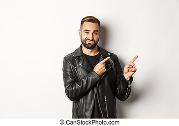 Skeptical and doubtful guy in black leather jacket, shrugging while pointing at upper right corner promo offer, standing over white background