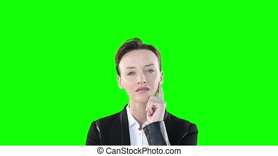 Skeptical Caucasian woman looking at camera on green background.