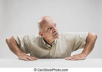Skeptical disbelieving senior man glaring