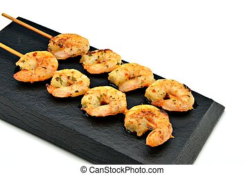 Skewer shrimp on black plate
