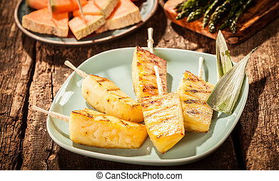 Skewers of Grilled Pineapple Wedges on Green Plate