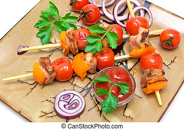 skewers of meat with vegetables on a plate - white background