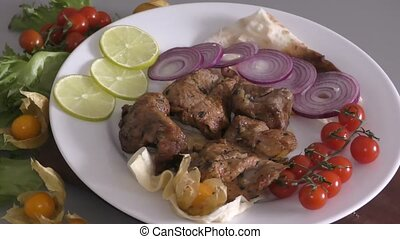 Skewers of pork meat with fresh Greens and vegetables
