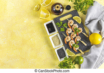 Skewers shrimp barbecue served on wood cutting board with lemon or lime in top view. Delicious grilled prawn with spices for snacks in party. Homemade food concept of seafood menu.