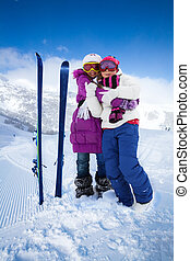 Ski buddies - Two cute kids girls hugging with skis and...