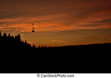 Ski chair lift in the mountains at red sunset