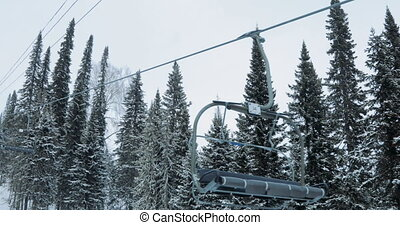 Ski chair-lift without skiers in snow-capped mountains - Ski...