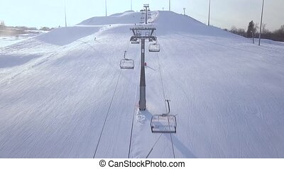 Ski elevator for transportation skiers and snowboarders on snow mountain in ski resort drone view. Ski lift with chair on snow slope drone view.