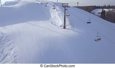 Ski elevator for transportation skiers and snowboarders on snow mountain in ski winter resort aerial view. Ski chairlift on rope way in snow slope drone view.