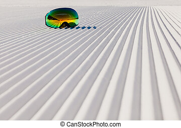 Ski goggles laying on a new groomed snow and empty ski slope...
