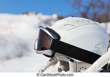 Ski helmet between poles in front of mountain