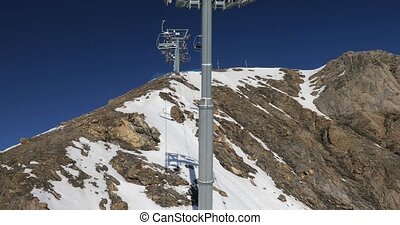 Using ski lift in the Alps, lack of snow on the top of the mountain after wind blowing it away