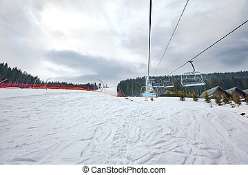 Ski lift at ski resort Bukovel in the mountains on a sunny winter day.