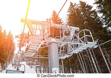 Ski lift at ski resort Bukovel in the mountains on a sunny winter day. Sun flare