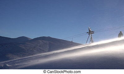 Ski lift moving up to the mountain.Snowboarders crossing...