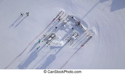 Ski lift on winter resort for transportation skiers and snowboarders on snow mountain drone view. People skiing on snowy mountain on ski resort aerial view.