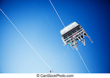 Ski lift carrying unrecognizable skiers up to the clear blue...