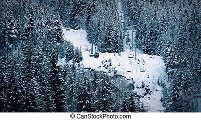 Ski Lift Through Trees On Slope - Wide shot of ski lift on...