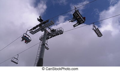 Ski Lift with Skiers on a Background of Blue Sky and Clouds. Ski Resort.