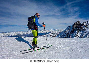 Ski mountaineer arrived at the top is ready for the descent