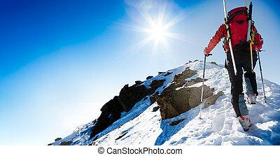 Ski mountaineer walking up along a steep snowy ridge with ...