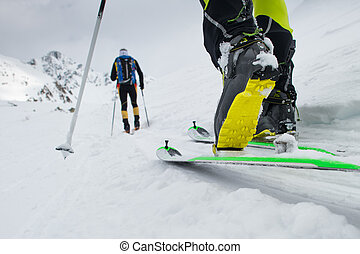 Ski mountaineering boot detail during ascent in the snow
