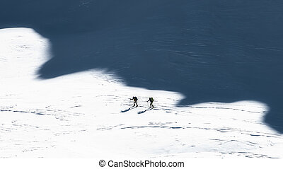 Ski mountaineers in the shadows of the mountains. Artistic style photo