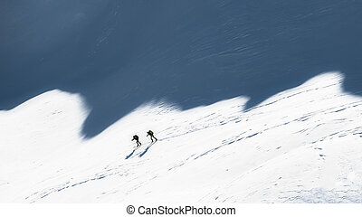 Ski mountaineers in the shadows of the mountains