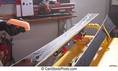 Snowboard tuning and reapair. Winter shop worker doing base repair. Rental workshop service