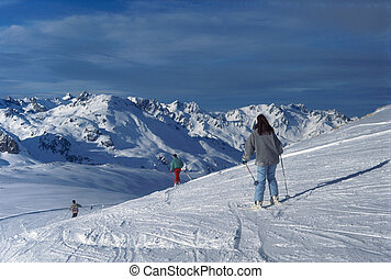 Skiers in ski resort, and snowed mountains in Savoy, France