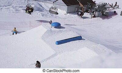 Ski resort. Snowboarders and skiers ride on springboard. Ski lifts. Sunny day.