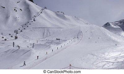 Ski resort. Snowboarders ride on slope. Skiers. Ski lifts. White snow. Sunny day