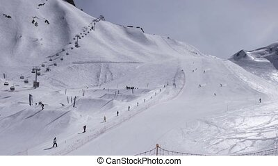 Ski resort. Snowboarders ride on slope. Skiers. Ski lifts. White snow. Sunny day
