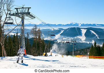 Ski resort - Snowborder going down the slope at ski resort