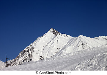 Ski slope and blue clear sky at sunny day