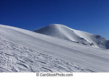 Ski slope and blue sky. Georgia, ski resort Gudauri. Caucasus Mountains.