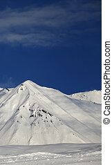 Ski slope and blue sky with clouds at sunny day