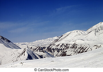 Ski slope and snowy mountains in sun day. Caucasus...