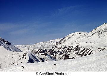 Ski slope and snowy mountains in sun day. Caucasus Mountains, Georgia, ski resort Gudauri.