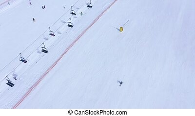 Ski slope - ski lift, skiers and snowboarders going down....