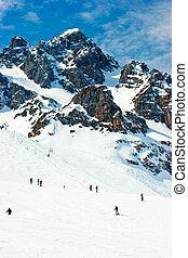Ski slope - Skiers on a piste at Alpine ski resort